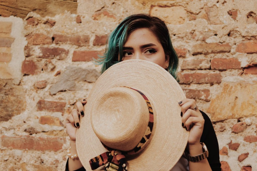 woman hiding face with hat embarrassed for not keeping resolutions