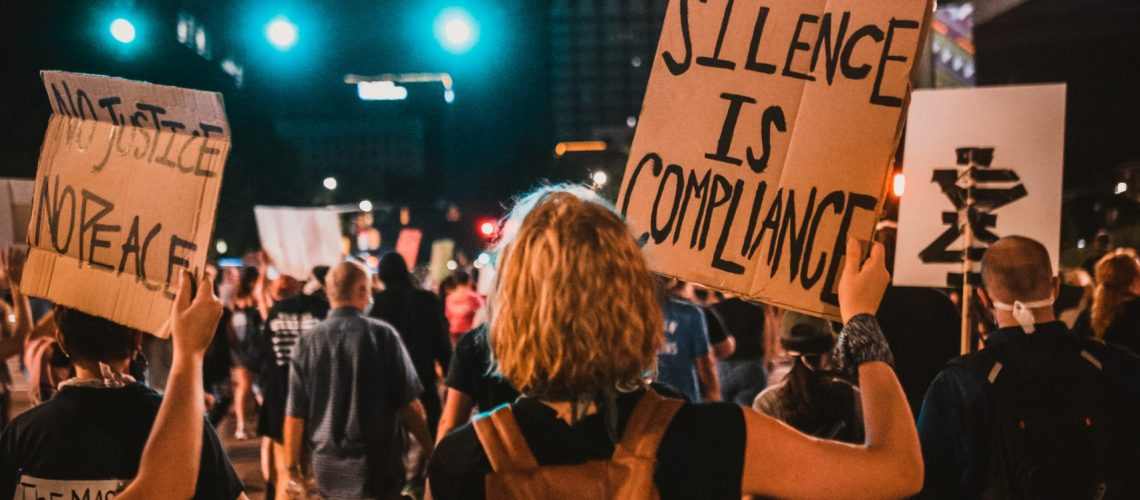 white woman holding sign at black protest silence is compliance