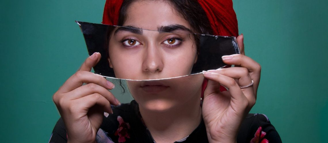 woman holding mirror shard in front of eyes with another woman's eyes reflected as comparison